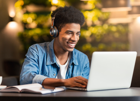 College boy on computer wearing headphones and smiling