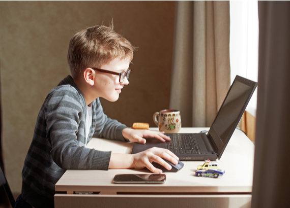 Young boy wearing glasses, at a desk talking to friends on a computer