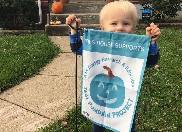 Kid with Teal Pumpkin sign