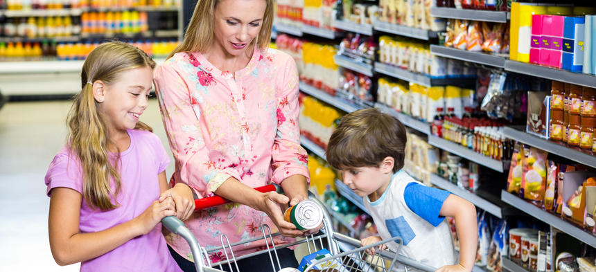 Mom in grocery store reading label on can with kids