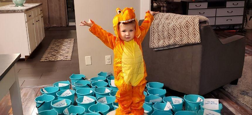Kid dressed as Dino with Teal Halloween Buckets